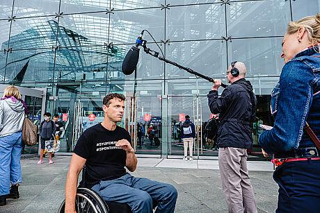 Ein Mann im Rollstuhl gibt einer Frau mit blauer Jeansjacke ein Interview in der Nähe vom Berliner Hauptbahnhof. Auf seinem schwarzen T-Shirt stehen die Hashtags #StufeMussWeg und #SpontanReisen
