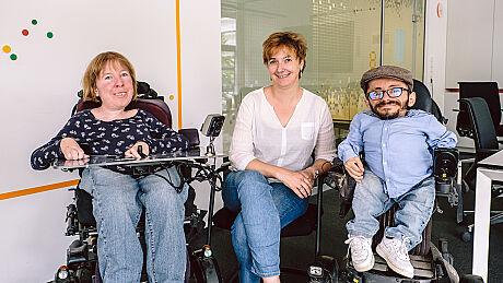 Drei Personen lächeln in die Kamera, zwei Personen sitzen im Rollstuhl.