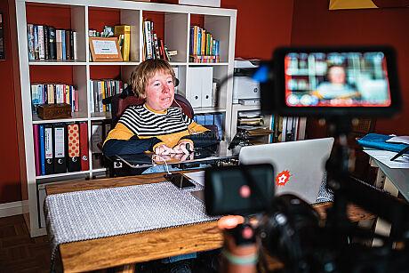 Anne Gersdorff sitzt vor einem Notebook in ihrem Büro. Eine Kamera filmt sie ab.
